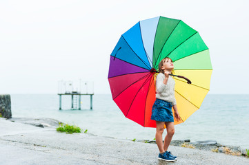 Portrait of a cute little girl with a big colorful umbrella