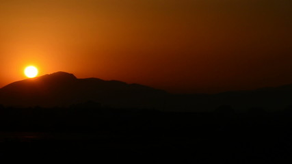 Timelapse of sunset with sun and mountains