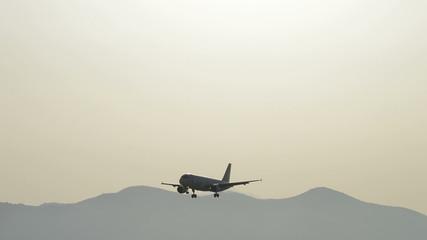 Big airplane landing at sunset