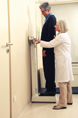 Man standing on weight machine with female doctor analyzing resu