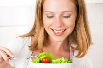 young happy woman eats vegetable salad