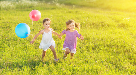 happy twin sisters running laughing  with balloons in summer