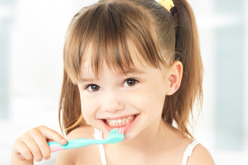happy little girl brushing her teeth