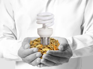 close up hand holding bulb and coins