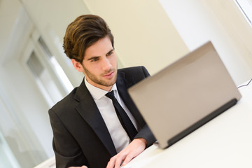 Businessman sitting at his laptop and working in his office