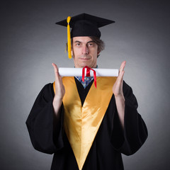 Man in an academic cap and gown with diploma in hand.