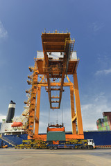 Container Cargo freight ship with working crane loading bridge