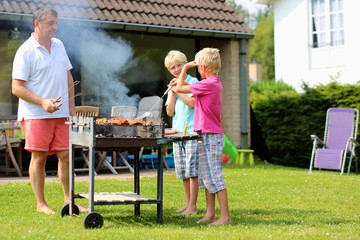 Father and kids making barbecue at the backyard of the house
