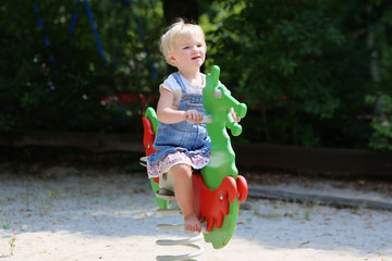 Happy little preschool girl having fun at playground