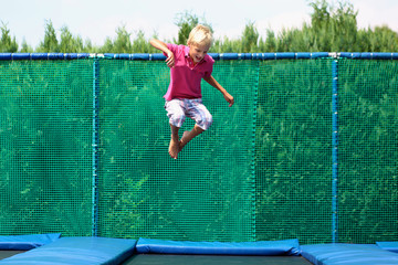 Happy teenage boy jumping on trampoline