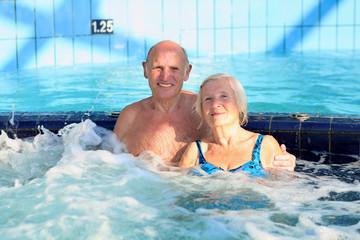 Happy seniors couple relaxing in swimming pool enjoying
