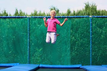 Happy teenage boy jumping on trampoline