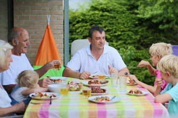 Big happy family enjoying dinner outdoors in the terracce