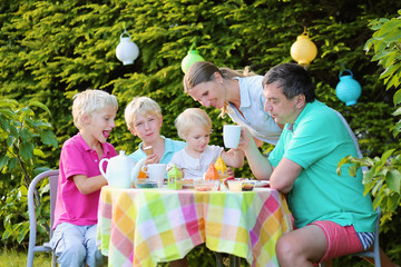 Happy family of five having lunch outdoors