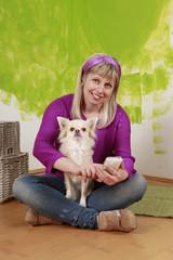 Junge Frau mit Chihuahua beim Simsen