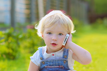 Adorable little girl talking by mobile phone