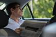 Businessman reading newspaper car