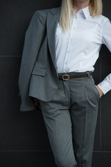 Unrecognizable business woman leaning wall