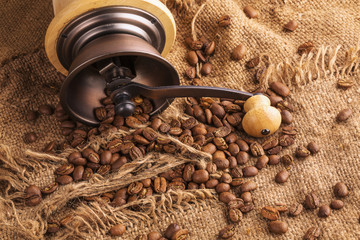 Coffee beans and old coffee mill on sacking