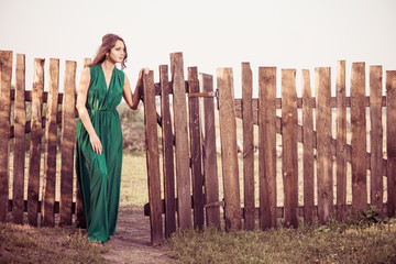 woman in green at vintage fence