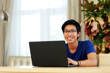 Happy asian man sitting at the table with laptop