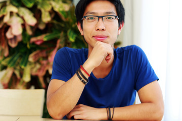 Happy asian man wearing glasses sitting at the table