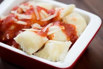 Close-up of ravioli with tomato sauce and parmesan, studio shot