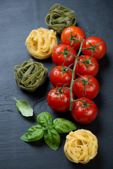 Red tomatoes on a branch, colored tagliatelle and green basil