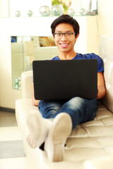 Cheerful asian man lying on the sofa with laptop at home