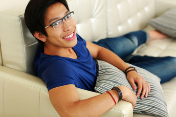 Smiling asian man relaxing at home on the sofa
