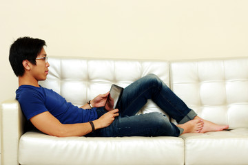 Portrait of a man lying on the sofa with tablet computer at home