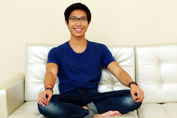 Smiling asian man relaxing at home sitting on sofa