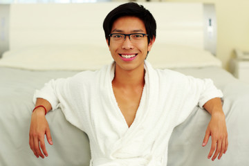 Happy man in bathrobe leaning on the bed in bedroom