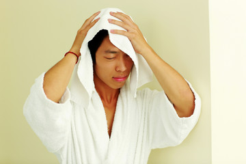 Asian man in bathrobe wiping face with a towel