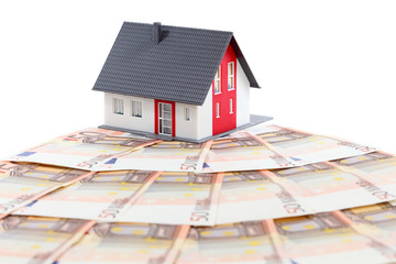 Model house and euro bills over white background