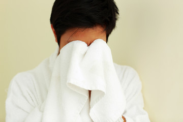 Young man in bathrobe wiping face with a towel