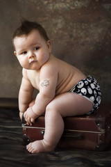 small boy sitting on suitcase