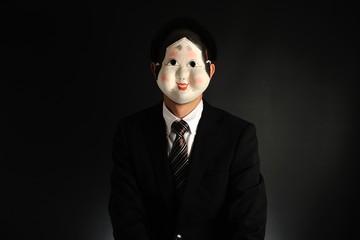 おかめのお面を被ったスーツのビジネスマン