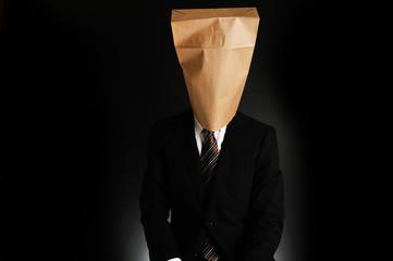紙袋で顔を隠したスーツのビジネスマンのポートレート