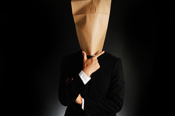 紙袋で顔を隠したスーツのビジネスマンが考えている様子
