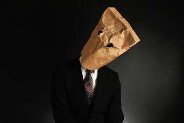 紙袋で顔を隠したスーツのビジネスマンの気分が落ち込んでいる様子