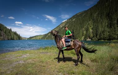 Travelling on horseback on a mountain lake