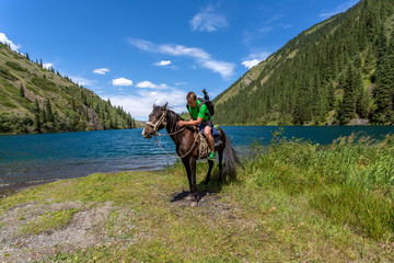 Travelling on horseback on a mountain lake