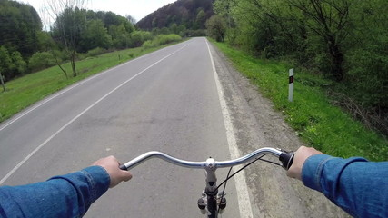 rides a bicycle on a country road