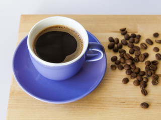 Cup of black coffee and grain of the fried coffee