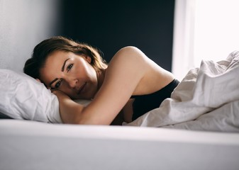 Young woman lying in bed daydreaming