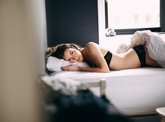 Female model in lingerie lying on her bed