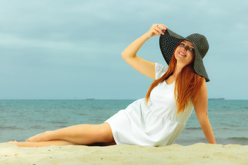 Beautiful redhaired girl in hat on beach, portrait