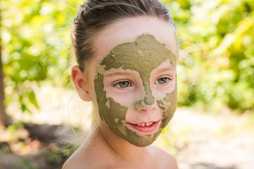 Close up of beautiful girl with facial clay mask