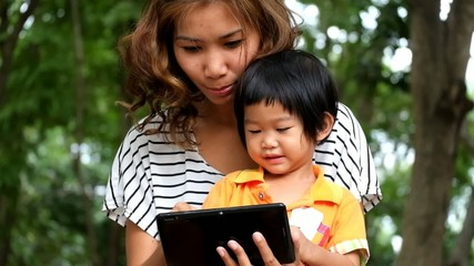 An asian boy and mother are playing funny game on tablet